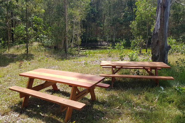 Two wooden picnic tables beside a dam