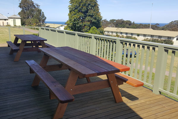 Two picnic tables on a deck overlooking Sydney