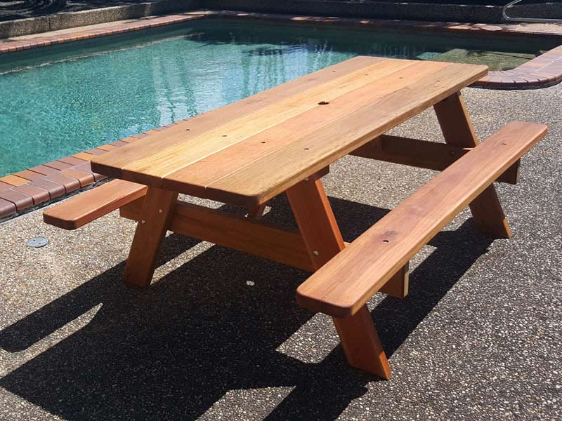 Wooden picnic table infront of an inground pool